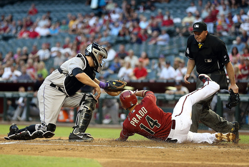 . Catcher Jordan Pacheco #58 of the Colorado Rockies tags out Martin Prado #14 of the Arizona Diamondbacks as he attempts to score a run during the first inning of the MLB game at Chase Field on April 30, 2014 in Phoenix, Arizona.  (Photo by Christian Petersen/Getty Images)