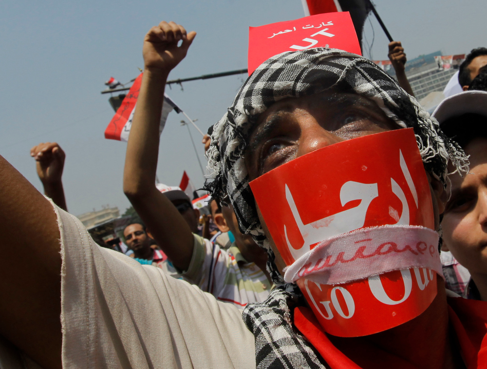 ". Opponents of Egypt\'s Islamist President Mohammed Morsi shout slogans during a protest in Tahrir Square in Cairo, Egypt, Wednesday, July 3, 2013. A Defense Ministry official said army chief Gen. Abdel-Fattah el-Sissi is meeting with his top commanders, hours before the military\'s deadline to the president and opposition to resolve the nation\'s political crisis is set to expire. Arabic reads ""Leave.\"" (AP Photo/Amr Nabil)"