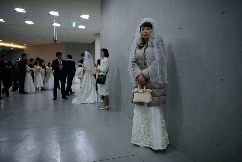 ". A bride waits for her groom prior to a mass wedding at an event held by the Unification Church in Gapyeong on February 12, 2014. Unification Church members forming 2500 couples from 52 countries were married in a mass wedding in South Korea -- only the second such event since the death of their ""messiah\"" and controversial church founder Sun Myung Moon. (ED JONES/AFP/Getty Images)"