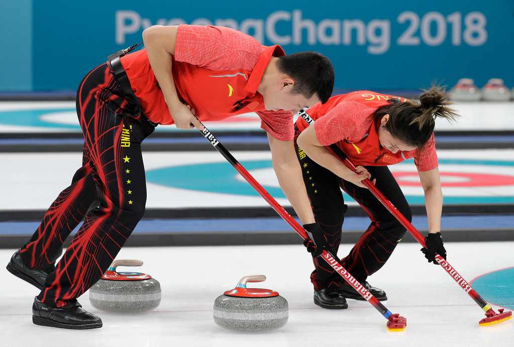 . China\'s Ba Dexin, left, and Wang Rui sweeps ice during their mixed doubles curling match against Norway at the 2018 Winter Olympics in Gangneung, South Korea, Sunday, Feb. 11, 2018. Norway won. (AP Photo/Aaron Favila)