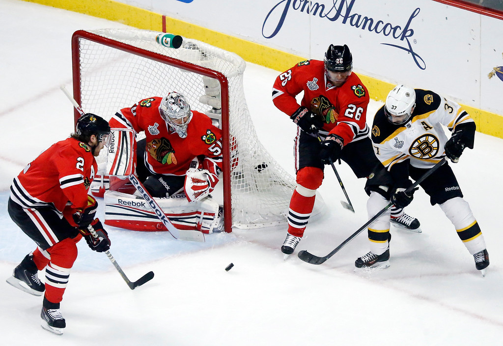 . Boston Bruins center Patrice Bergeron (37) takes a shot against Chicago Blackhawks defenseman Duncan Keith (2), goalie Corey Crawford (50) and center Michal Handzus (26) during the first period of Game 1 in their NHL Stanley Cup Final hockey series on Wednesday, June 12, 2013, in Chicago. (AP Photo/Charles Rex Arbogast)