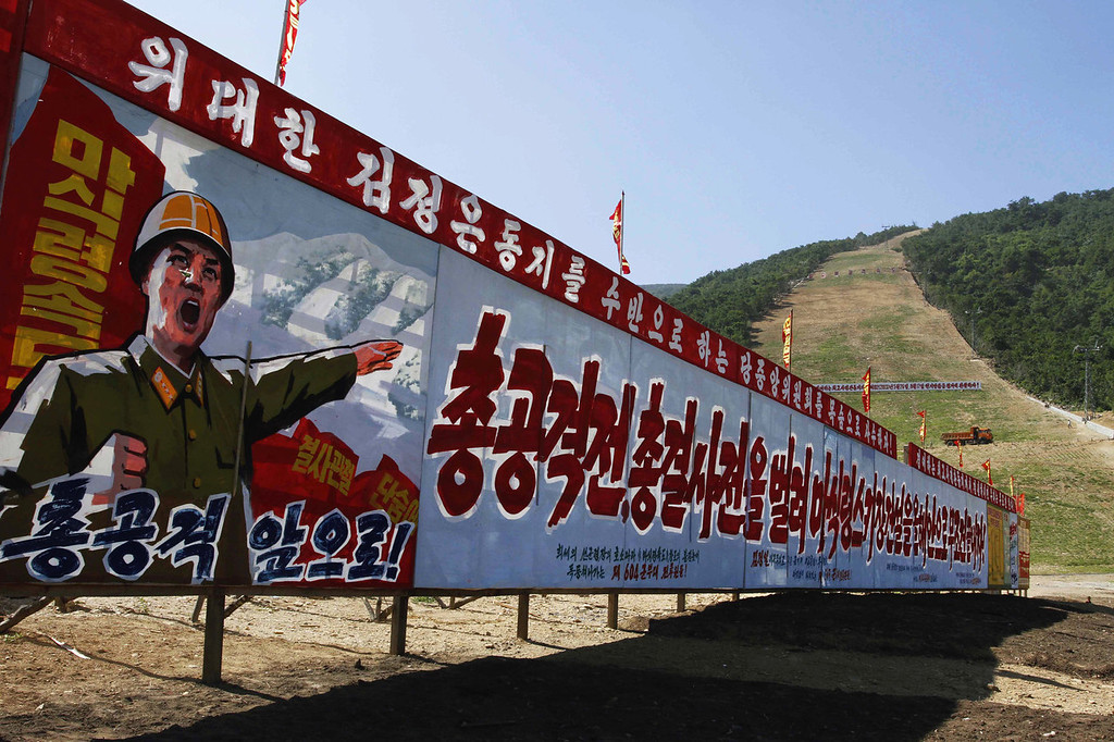 ". North Korean propaganda stands at the base of a ski slope at a ski resort building project at North Korea\'s Masik Pass on Aug. 23, 2013. The sign reads, from left to right, ""Full attack. March Forward. Let\'s Absolutely Finish Building Masik Pass Ski Resort Within This Year By Launching A Full Aggressive War and Full Battle.\""  (AP Photo/Kim Kwang Hyon)"