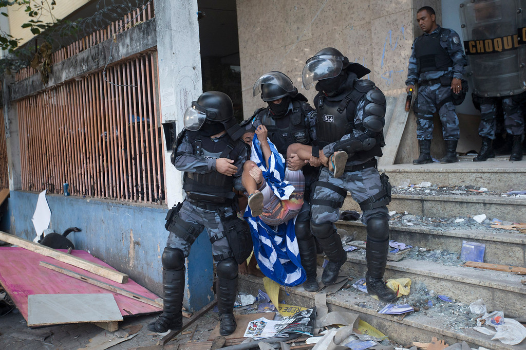 . Police officers carry a squatter during an eviction from an abandoned building in Rio de Janeiro, Brazil, Thursday, April 10, 2014. Squatters in Rio de Janeiro are clashing with police after a Brazilian court ordered that 5,000 people be evicted from abandoned buildings of a telecommunications company. Officers have used tear gas and stun grenades to try to disperse the families.(AP Photo/Silvia Izquierdo)