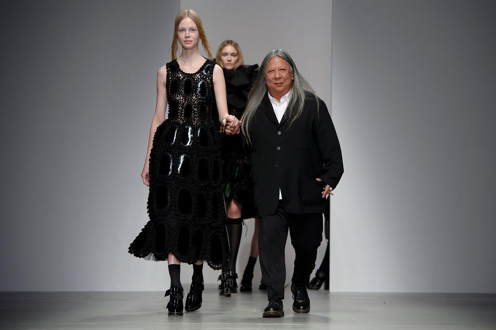 . Hong Kong born designer John Rocha, right, walks the runway,  during his London Fashion Week Autumn/Winter 2014 show, at Somerset House in central London, Saturday, Feb. 15, 2014. (Photo by Jonathan Short/Invision/AP)