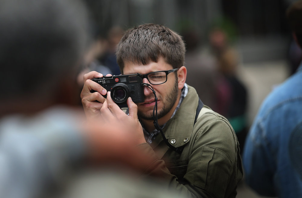 . Former Chicago Sun-Times photographer Andrew Nelles shoots pictures of his former colleagues during a demonstration outside the offices of the Sun-Times on June 6, 2013 in Chicago, Illinois. Union members, reporters, and photographers gathered outside the newspaper\'s office to protest the company\'s decision last week to eliminate its 28-member photo staff. The newspaper chain plans to train their reporters to take pictures with iPhones to fill the void.  (Photo by Scott Olson/Getty Images)
