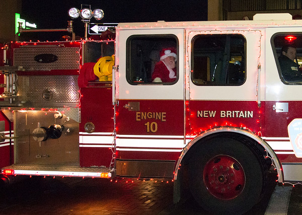 12/05/19 Wesley Bunnell | StaffrrThe New Britain Christmas tree was lit on Thursday night in Central Park complete with a visit from Santa Clause who rode in on a NBFD fire truck. Santa prepares to exit Engine 10.