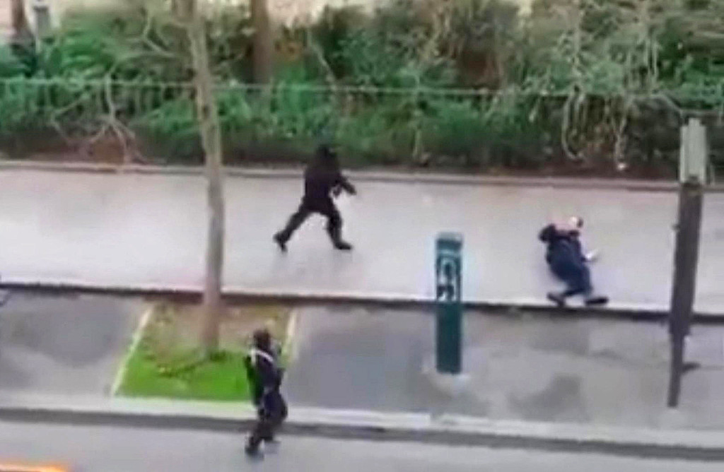 . Masked gunman run towards a victim of their gun fire  outside the  French satirical newspaper Charlie Hebdo\'s office, in Paris, Wednesday, Jan. 7, 2015. Paris residents captured chilling video images of two masked gunmen shooting a police officer after an attack at a French satirical newspaper. In the video, the gunmen armed with assault rifles are seen running up to an injured police officer, who lies squirming on the ground. The police officer raises his hands up before one of the assailants shoots him in the head at a close range.  (AP Photo) NO SALES