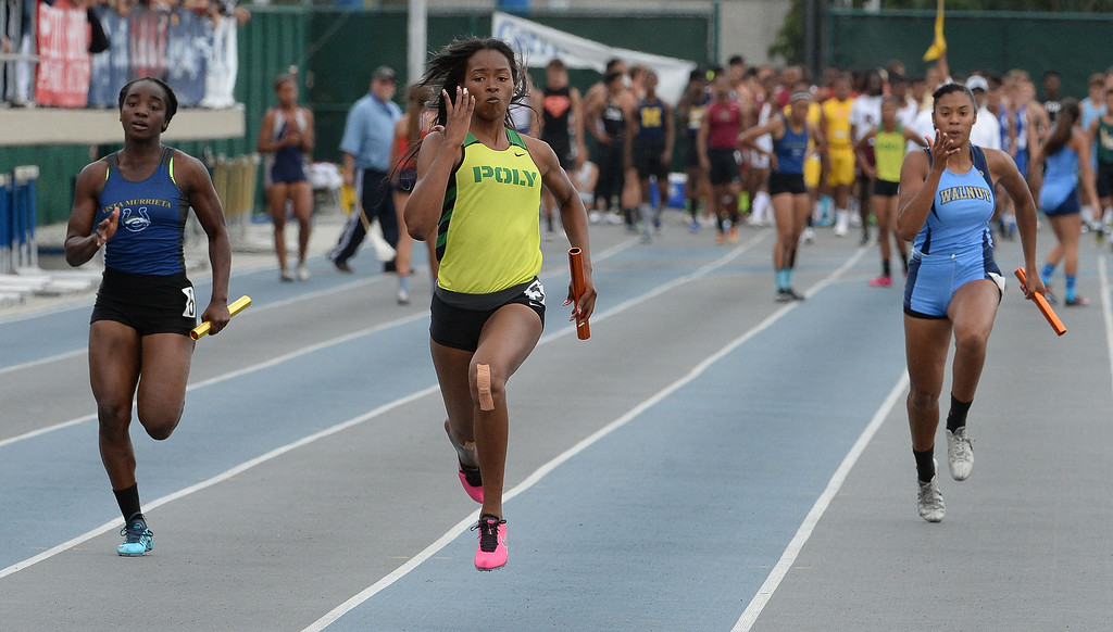 . Long Beach Poly\'s Arianna Washington runs the final leg of the Division 1 4x100 meter run along with Walnut\'s Victoria Sandoval during the CIF Southern Section track and final Championships at Cerritos College in Norwalk, Calif., on Saturday, May 24, 2014. Long Beach poly won the race.   (Keith Birmingham/Pasadena Star-News)