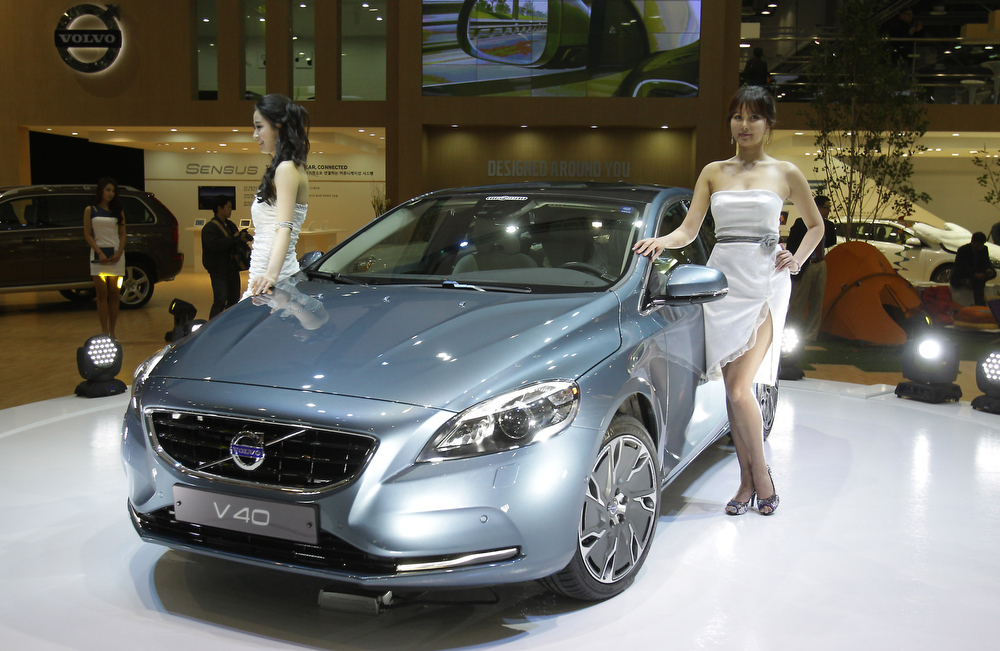 . Models pose next to a Volvo V40 at the Seoul Motor Show 2013 on March 28, 2013 in Goyang, South Korea. The Seoul Motor Show 2013 will be held in March 29-April 7, featuring state-of-the-art technologies and concept cars from global automakers. The show is its ninth since the first one was held in 1995. About 384 companies from 14 countries, including auto parts manufacturers and tire makers, will set up booths to showcase trends in their respective industries, and to promote their latest products during the show.  (Photo by Chung Sung-Jun/Getty Images)