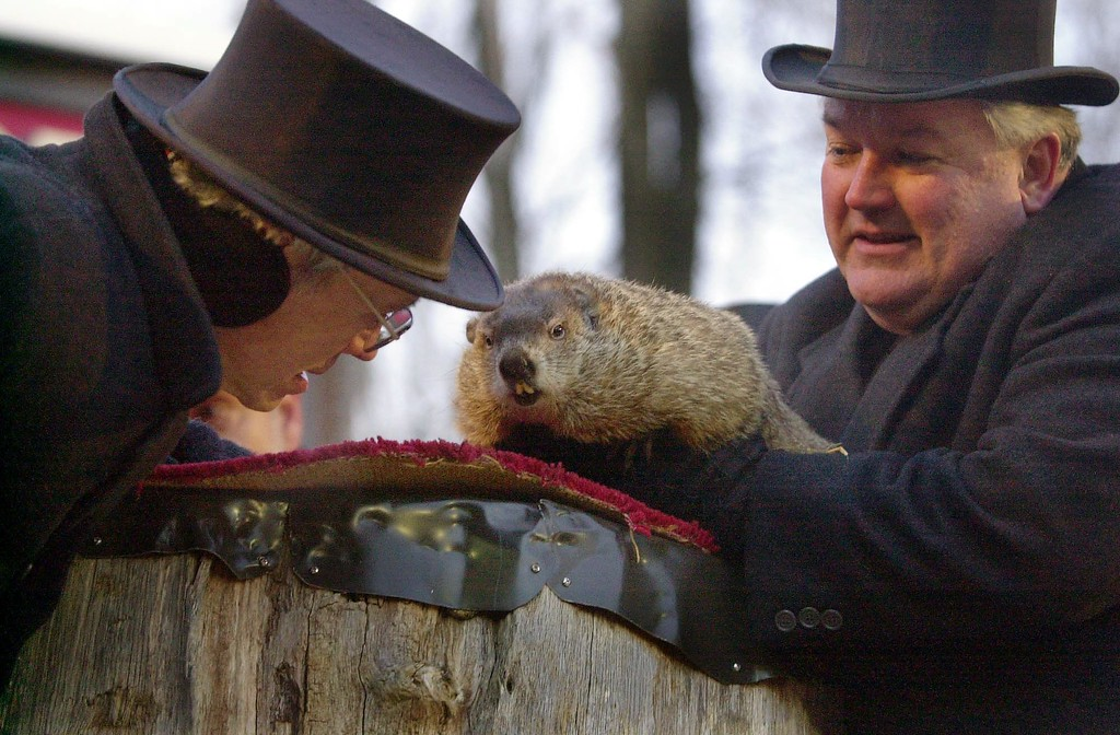 . Punxsutawney Phil, the weather prognosticating groundhog from Gobblers Knob in Punxsutawney, Pa., center, is held by handler Bill Deeley, right, as he tells Punxsutawney Groundhog Club President Bill Cooper, left, he saw his shadow upon emerging from his burrow at 7:27 a.m., Monday, Feb. 2, 2004, and predicted  six more weeks of winter. (AP Photo/Gene J. Puskar)