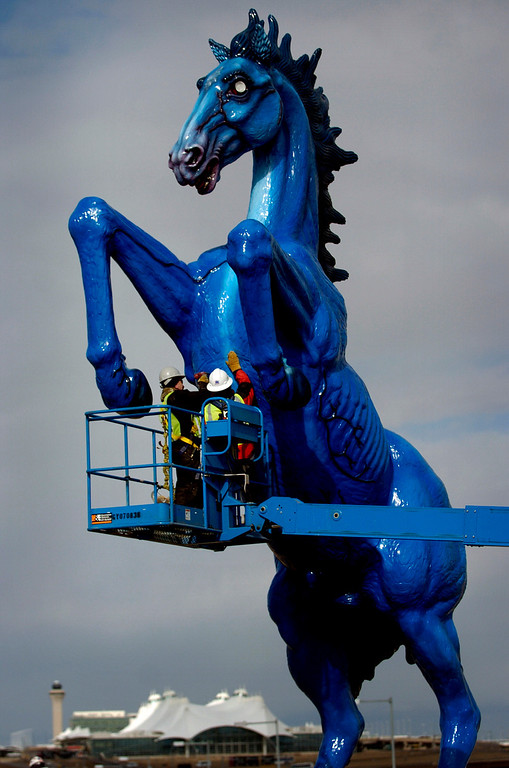 """. Workers John Van Aucken, left, and Serge Labesque, right, work on an access plate on the chest of the 32 foot tall fiberglass \""""Mustang\"""" by artist Luis Jimenez that is being installed outside of Denver International Airport  on Tuesday, February 12, 2008. Fifteen years after Jimenez began sculpting the rearing mustang that later fell from a hoist and killed him, the towering statute is taking its place on Peña Boulevard. Jimenez died June 13, 2006, when a large piece of the sculpture slipped from the hoist he used to move it and pinned him against a steel support beam in his Hondo, N.M., studio. City officials commissioned \""""Mustang\"""" from Jimenez in 1992 at a cost of $300,000. (Cyrus McCrimmon/The Denver Post)"""
