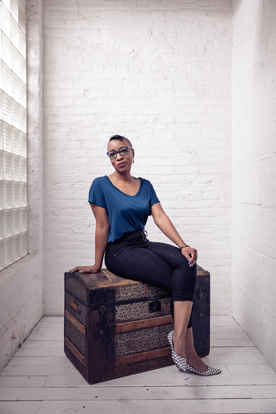 A female portrait of an African American sitting on top of a storage chest.