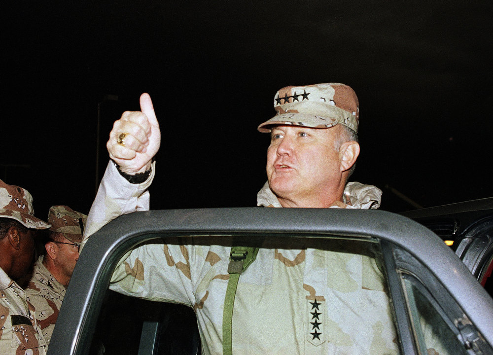 Description of . U.S. Army General Norman Schwarzkopf gives a thumbs up sign to the crowd along the beach at Kuwait City on Tuesday, March 12, 1991, after an impromptu tour of the area. While on the beach, Schwarzkopf filled a small bottle with sand and posed for pictures. This picture was made at noon with the sky blackened by oil smoke. (AP Photo/Michel Lipchitz)