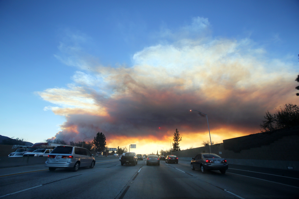 . Commuters make their way along the 210 freewa as a wildfire burns in the hills just north of the San Gabriel Valley community of Glendora, Calif. on Thursday, Jan 16, 2014. Southern California authorities have ordered the evacuation of homes at the edge of a fast-moving wildfire burning in the dangerously dry foothills of the San Gabriel Mountains. (AP Photo/Ringo H.W. Chiu)