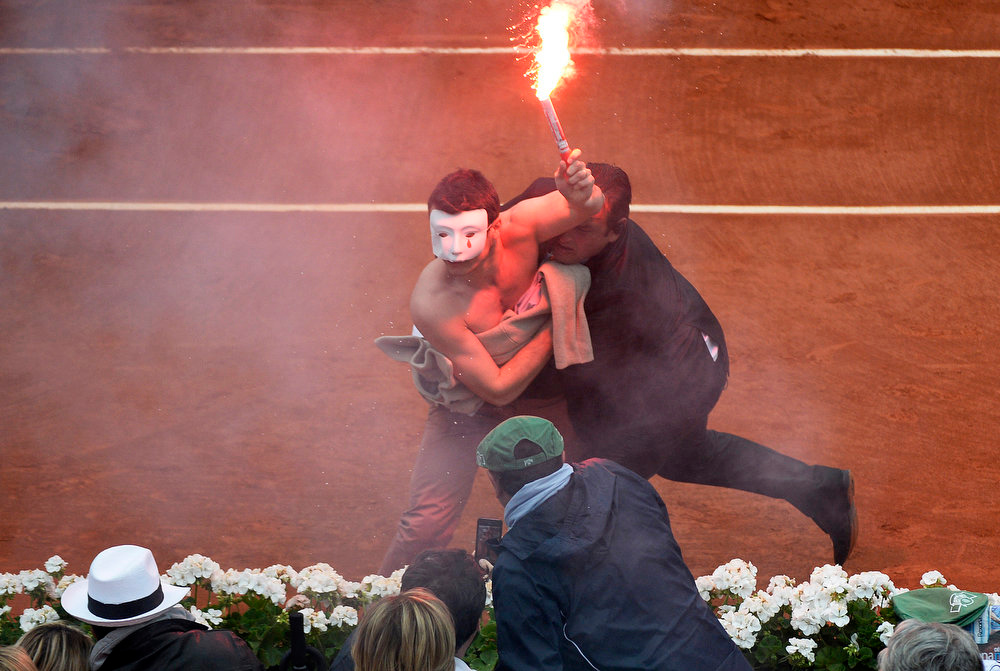 . An anti gay-marriage activist holding a flare is evacuated by a member of the security as he protest on the central court during the 2013 French tennis Open final match at the Roland Garros stadium in Paris on June 9, 2013.  MARTIN BUREAU/AFP/Getty Images
