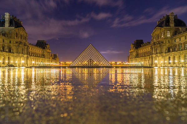 iew of famous Louvre Museum with Louvre Pyramid at evening