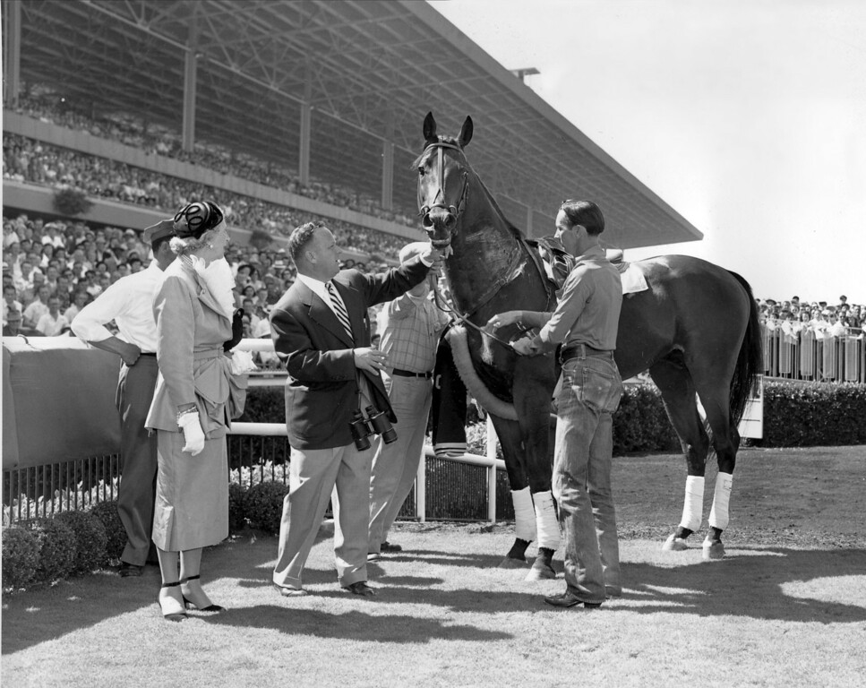 ". Citation is shown in the winner\'s circle after taking a bow at Hollywood Park in Inglewood, Ca., on July 21, 1951.  Citation, the first race horse to win $1 million, was retired to stud on July 20.  Standing with ""Big Cy,\"" from left, are, owner Lucille Parker Wright, trainer Jimmy Jones, holding bridle, and exercise boy Freeman McMillen.   (AP Photo)"