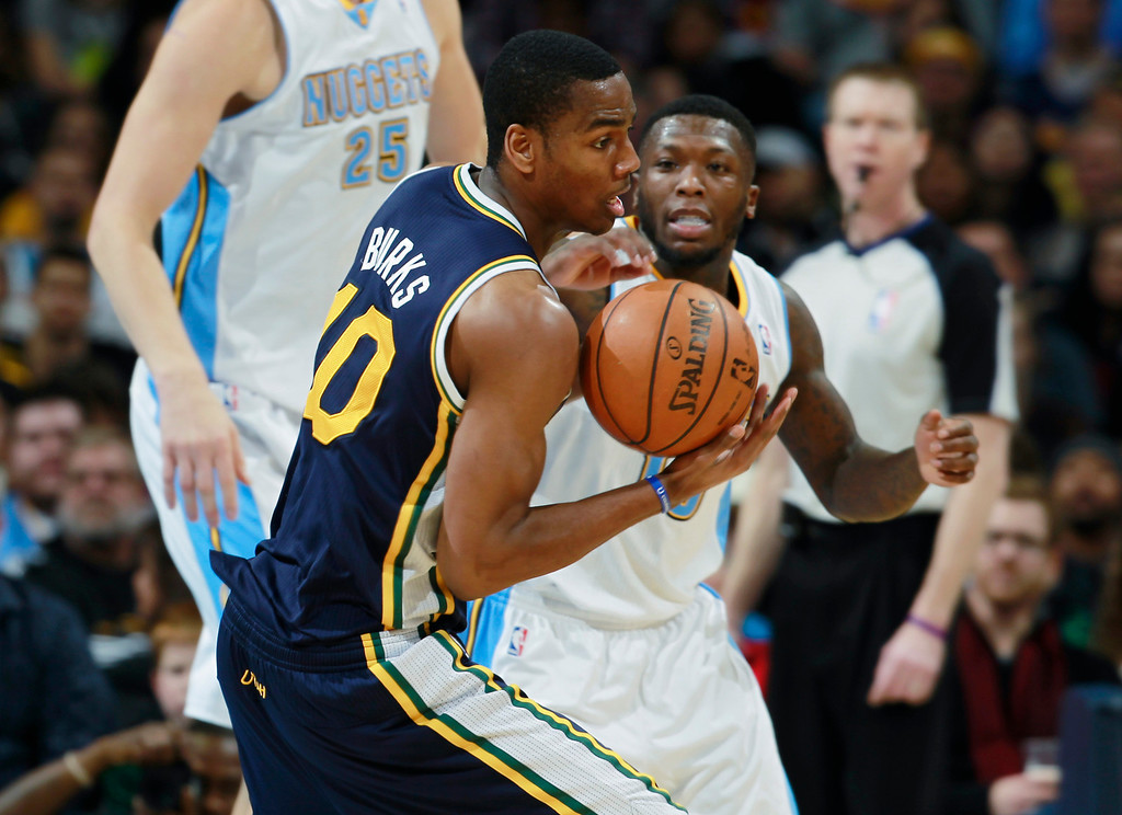 . Utah Jazz guard Alec Burks, front, pulls in a loose ball in front of Denver Nuggets guard Nate Robinson in the fourth quarter of Utah\'s 103-93 victory in an NBA basketball game in Denver on Friday, Dec. 13, 2013. (AP Photo/David Zalubowski)