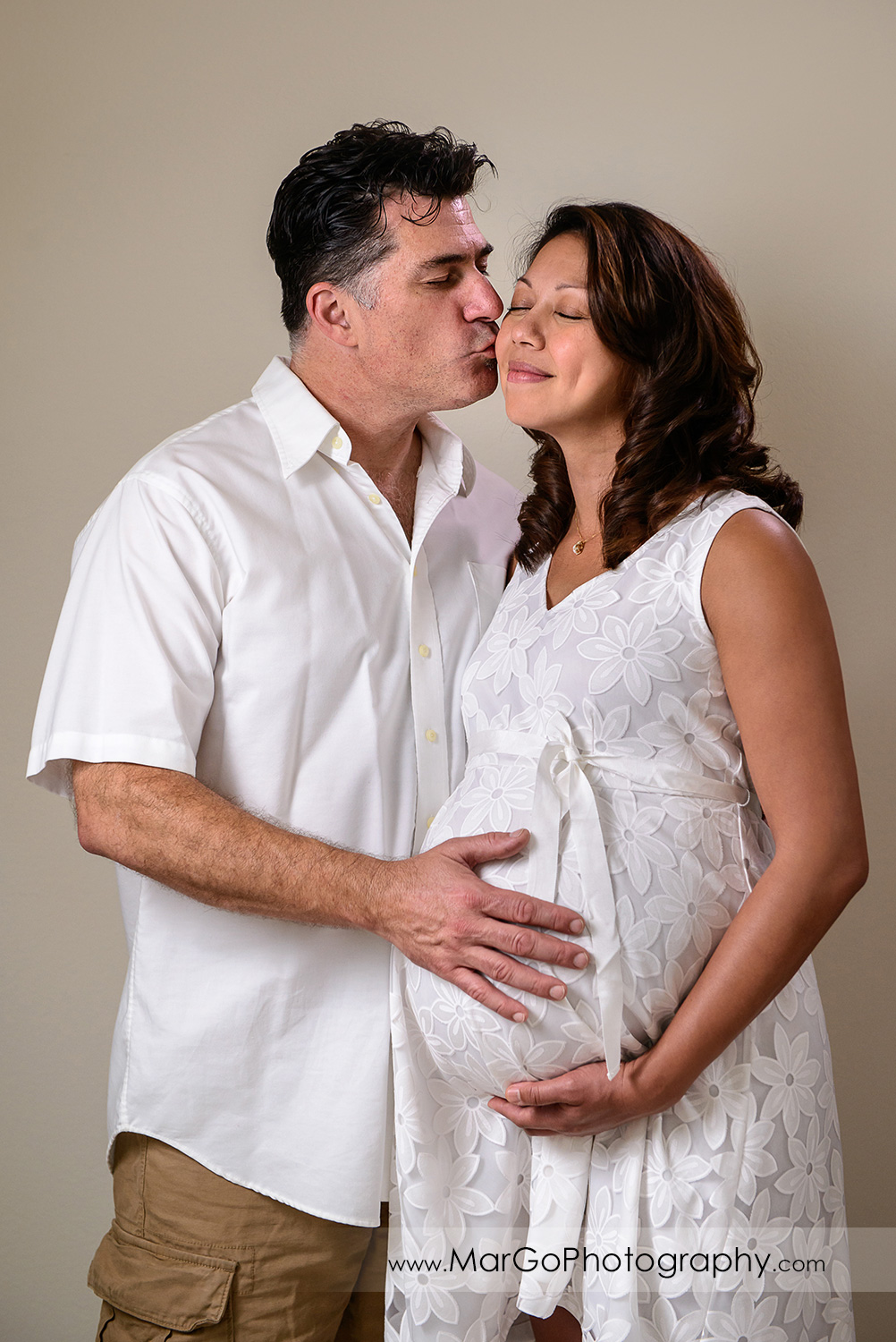 man in white shirt kissing pregnant woman in white dress during maternity session