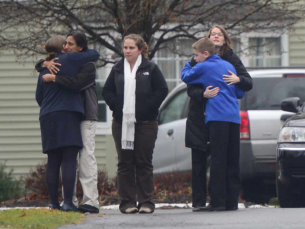 Description of . Mourners embrace December 17, 2012 at the funeral for Jack Pinto, 6, one of the victims of the December 14, Sandy Hook elementary school shooting, in Newtown, Connecticut.  Funerals began Monday in the little Connecticut town of Newtown after the school massacre that took the lives of 20 small children and six staff, triggering new momentum for a change to America's gun culture.  AFP PHOTO/Emmanuel  DUNAND/AFP/Getty Images