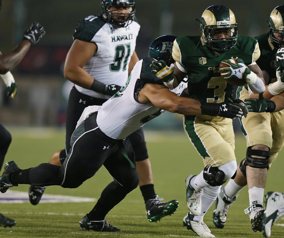. Hawaii linebacker Tevita Lataimua, left, pulls down Colorado State running back Treyous Jarrells after a short gain in the first quarter of an NCAA college football game in Fort Collins, Colo., on Saturday, Nov. 8, 2014. (AP Photo/David Zalubowski)