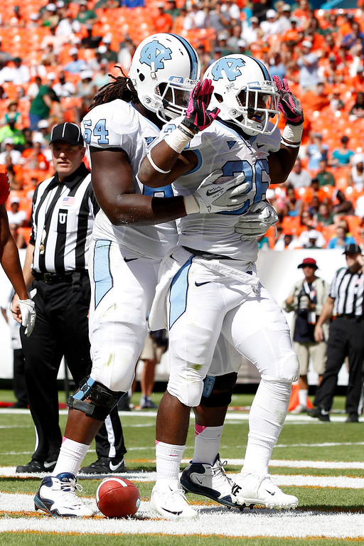 . Jonathan Cooper #64 of the North Carolina Tar Heels congratulates teammate Giovani Bernard #26 after Bernard scored a touchdown against the Miami Hurricanes on October 13, 2012 at Sun Life Stadium in Miami Gardens, Florida. (Photo by Joel Auerbach/Getty Images)