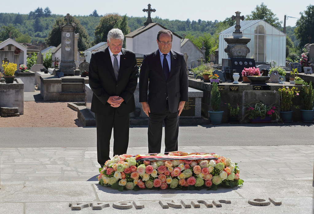. France\'s President Francois Hollande, right, and German President Joachim Gauck, left, pay respect after laying a wreath at the cemetery of the French martyr village of Oradour-sur-Glane, southwestern France, Wednesday, Sept. 4, 2013. Holding hands in quiet tribute, the presidents of Germany and France are visiting the scene of the largest massacre in Nazi-occupied France nearly seven decades ago. Wednesday\'s visit by German President Joachim Gauck to the southwestern French town of Oradour-sur-Glane is the first by a serving German leader. (AP Photo/ Phillipe Wojazer, Pool)