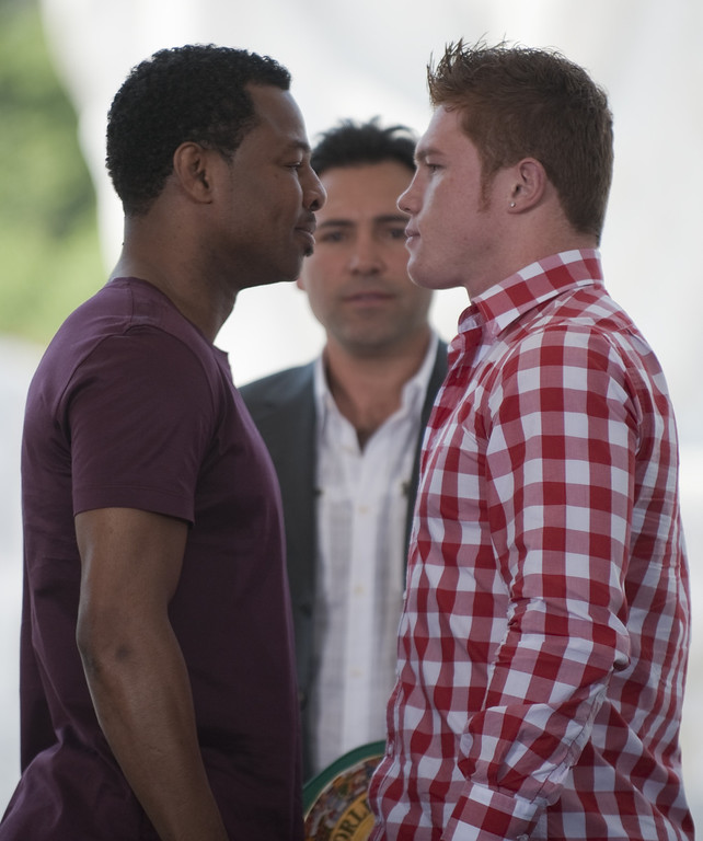 ". Mexican boxer Saul Alvarez (R) aka ""Canelo\"" and US boxer Sugar Shane Mosley face each other while US former boxer and promoter Oscar de la Hoya (C) looks on, after a press conference in Mexico city on March 08,2012. Mosley will face Alvarez on May 05.  (JOHAN ORDONEZ/AFP/Getty Images)"