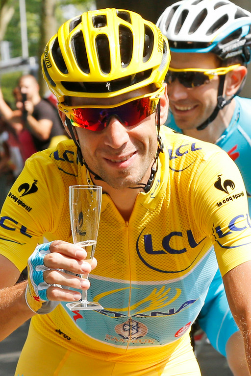 . Italy\'s Vincenzo Nibali, wearing the overall leader\'s yellow jersey, celebrates with a glass of champagne during the twenty-first and last stage of the Tour de France cycling race over 137.5 kilometers (85.4 miles) with start in Evry and finish in Paris, France, Sunday, July 27, 2014. (AP Photo/Jean-Paul Pelissier, Pool)