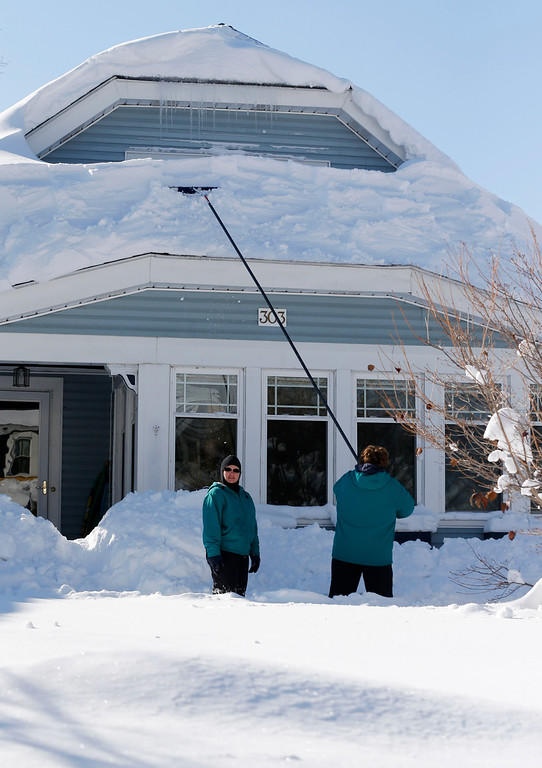 . People get snow off the roof of a house in the south Buffalo area on Friday, Nov. 21, 2014, in Buffalo, N.Y. A snowfall that brought huge drifts and closed roads in the Buffalo area finally ended Friday, yet residents still couldn\'t breathe easy, as the looming threat of rain and higher temperatures through the weekend and beyond raised the possibility of floods and more roofs collapsing under the heavy loads. (AP Photo/Mike Groll)