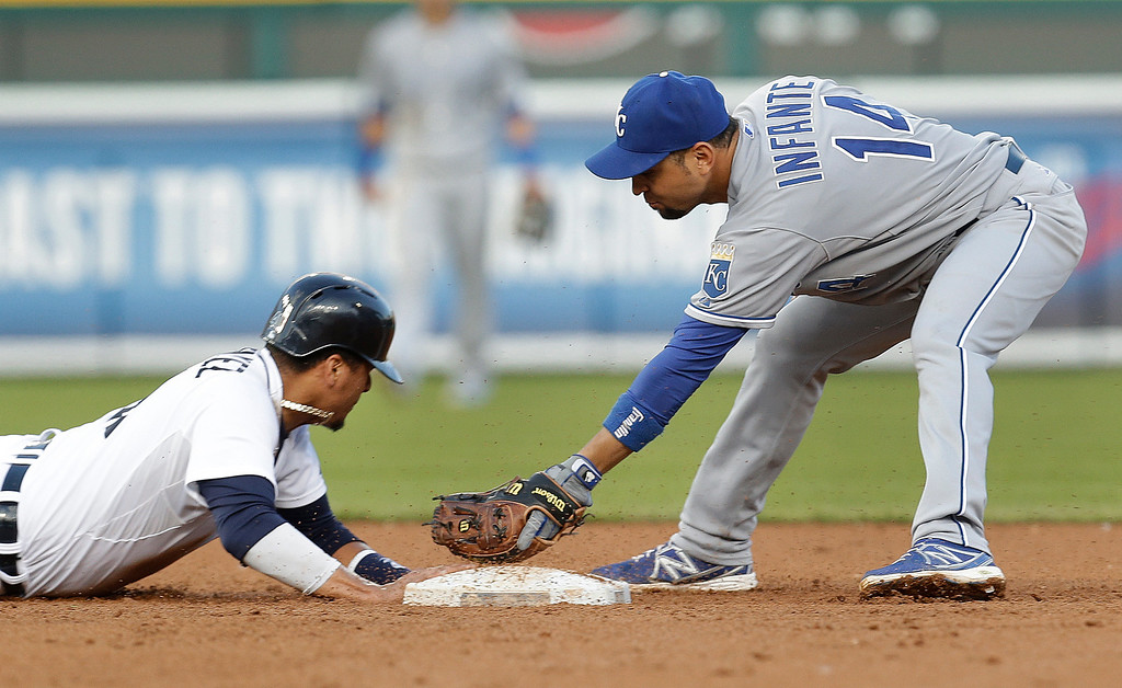 . Detroit Tigers Victor Martinez, left,  dives back into second base under the tag of Kansas City Royals second baseman Omar Infante, right, on Torii Hunter single in the fourth inning of a baseball game in Detroit, Monday, June 16, 2014.  (AP Photo/Paul Sancya)