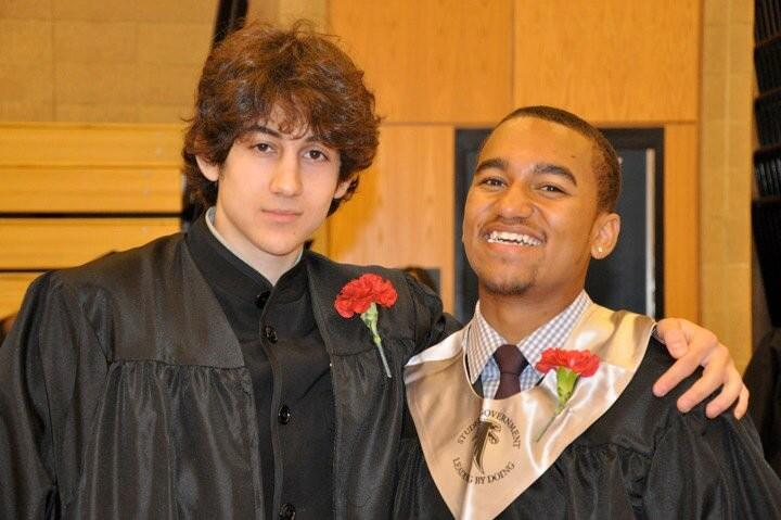 Description of . In this undated photo provided by Robin Young, Dzhokhar A. Tsarnaev, left, and Here & Now host Robin Youngís nephew, right, pose for a photo after graduating from Cambridge Rindge and Latin High School. Tsarnaev has been identified as the surviving suspect in the marathon bombings. Two suspects in the Boston Marathon bombing killed an MIT police officer, injured a transit officer in a firefight and threw explosive devices at police during a getaway attempt in a long night of violence that left one of them dead and another still at large Friday, April 19, 2013. (AP Photo/Robin Young)