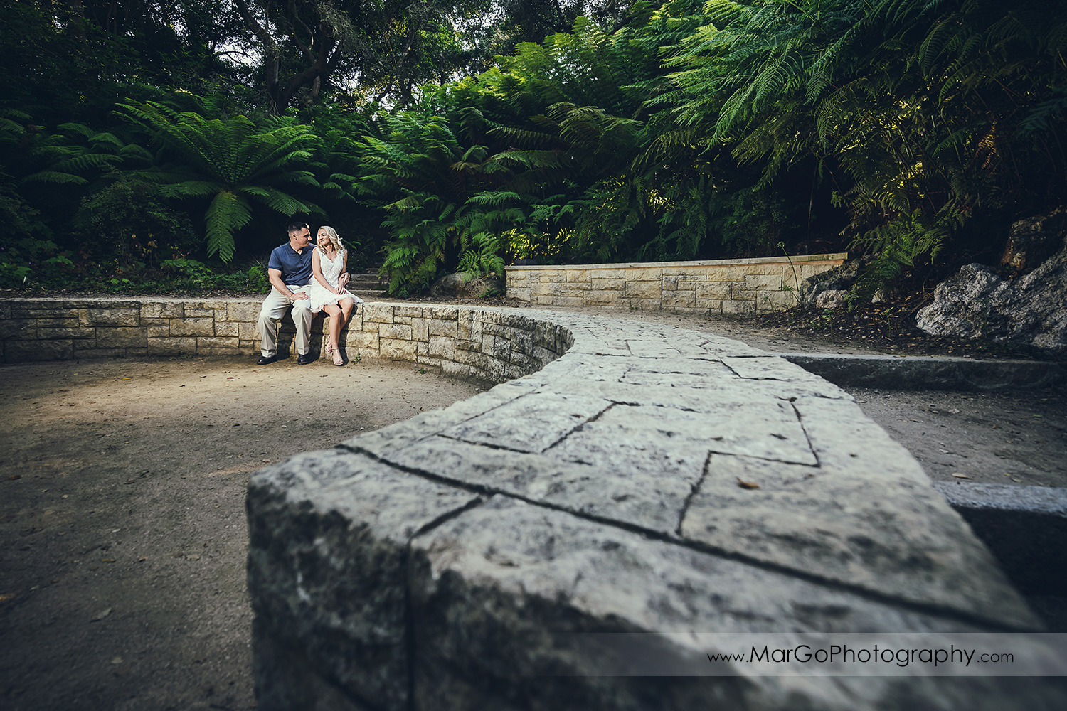 wide angle portrait of man in navy blue shirt and woman in white dress sitting on stone wall during engagement session at San Francisco Golden Gate Park