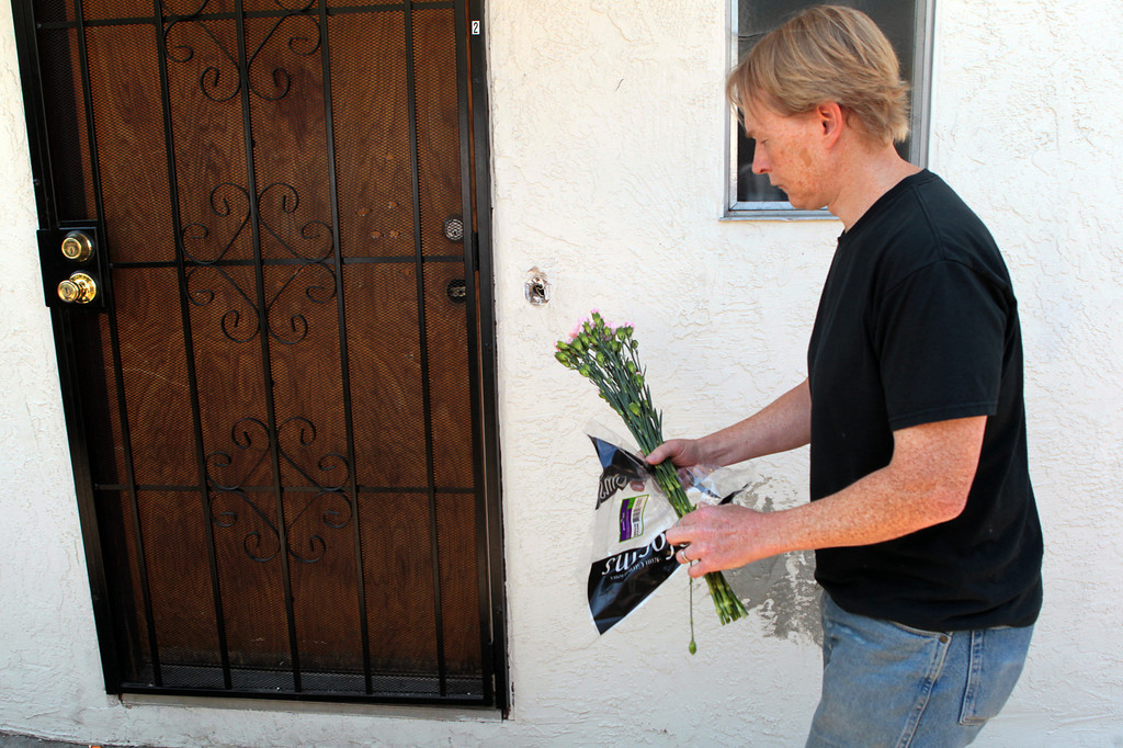 . Hugh Morrison, of Oakland, drops off flowers outside the home where an 8-year-old girl was killed in a shooting that also injured two other children and an adult on Wilson Avenue in Oakland, Calif., on Thursday, July 18, 2013.   (Anda Chu/Bay Area News Group)