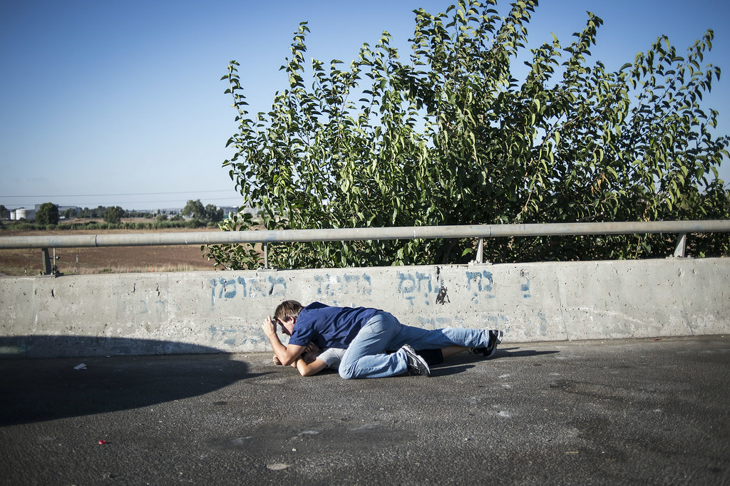 . Israelis seen taking cover on a highway as a siren sounds on July 17, 2014 in Tel-aviv, Israel. As the Israeli operation \'Protective Edge\' enters it\'s tenth day, the body count in Gaza has reach over 200 people. One Israeli has been killed in a Mortar attack.  (Photo by Ilia Yefimovich/Getty Images)