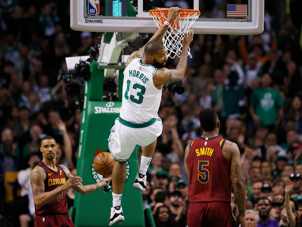 . Boston Celtics forward Marcus Morris (13) dunks against Cleveland Cavaliers guards George Hill (3) and JR Smith (5) in the second quarter of Game 1 of the NBA basketball Eastern Conference Finals against the Cleveland Cavaliers, Sunday, May 13, 2018, in Boston. (AP Photo/Michael Dwyer)