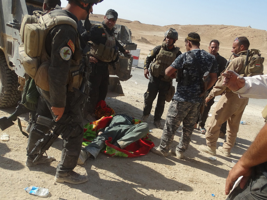 . Iraqi security forces and Sunni tribesmen stand next to Ahmed al-Dulaimi (C), the governor of Iraq\'s Anbar province, laying on the ground after he was injured during an attack at a military post he was visiting on September 7, 2014 on the road between Barwanah and Haditha in Anbar province, west of the provincial capital Ramadi. Dulaimi was injured during the attack, which also wounded Abdulhakim al-Jughaifi, the administrative official responsible for Haditha, and seven soldiers, shortly after the town of Barwanah was retaken from militants, an AFP journalist said. A suicide bomber then struck the convoy carrying Dulaimi toward Haditha for treatment, killing one soldier and wounding six. AFP PHOTO / AZHAR SHALLALAZHAR SHALLAL/AFP/Getty Images