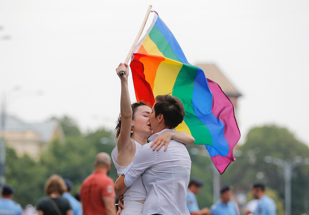 . Two girls kiss holding a rainbow flag during the gay pride parade in Bucharest, Romania, Saturday, June 9, 2018. People taking part in the gay pride parade in the Romanian capital demanded more rights and acceptance for same-sex couples. (AP Photo/Vadim Ghirda)