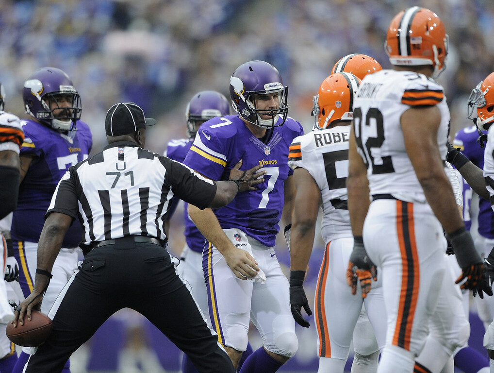 . Umpire Ruben Fowler #71 holds back Christian Ponder #7 of the Minnesota Vikings during the second quarter of the game on September 22, 2013 at Mall of America Field at the Hubert H. Humphrey Metrodome in Minneapolis, Minnesota. (Photo by Hannah Foslien/Getty Images)