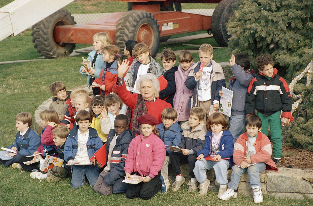 . Barbara Bush, left, the wife of President-elect George Bush, poses with school children after she placed the main ornament atop the 35-foot living National Christmas Tree, Thursday, Dec. 1, 1988 on the Ellipse in Washington. (AP Photo/Charles Tasnadi)