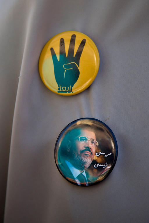 """. A supporter of Egypt\'s ousted President Mohammed Morsi wears buttons showing Morsi and an open palm with four raised fingers, which has become a symbol of the Rabaah al-Adawiya mosque, where Morsi supporters had held a sit-in for weeks that was violently dispersed in August, during a protest in Cairo, Egypt, Friday, Oct. 11, 2013. Thousands of Morsi supporters took to the streets Friday in several cities, commemorating 100 days since Egypt\'s first democratically elected president was ousted by the military following mass protests calling for his resignation. The Arabic on the button reads,\""""Rabaah, up, Morsi my president.\"""" (AP Photo/Hassan Ammar)"""