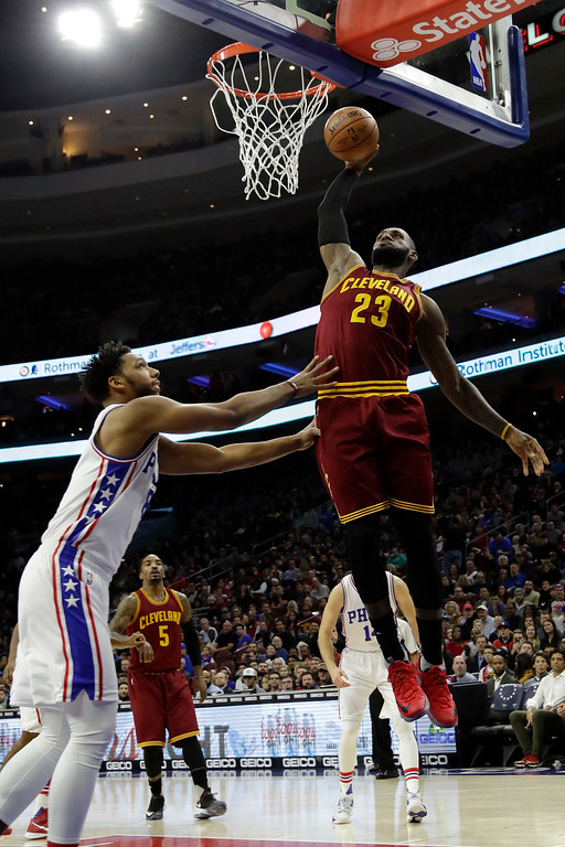 . Cleveland Cavaliers\' LeBron James, right, goes up for a dunk against Philadelphia 76ers\' Jahlil Okafor during the first half of an NBA basketball game, Sunday, Nov. 27, 2016, in Philadelphia. (AP Photo/Matt Slocum)