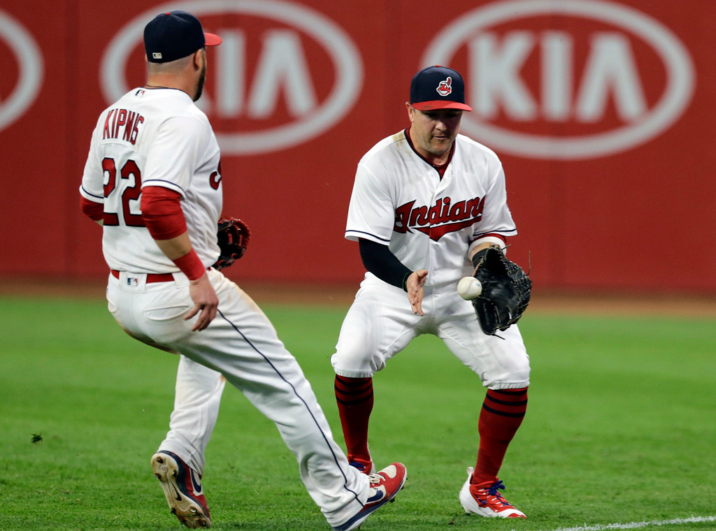 . Cleveland Indians\' Daniel Robertson fields a ball hit by Los Angeles Dodgers\' Yasmani Grandal during the eighth inning of a baseball game, Tuesday, June 13, 2017, in Cleveland. Grandal was out at second base as he tried to stretch a single into a double. Jason Kipnis is at left. (AP Photo/Tony Dejak)