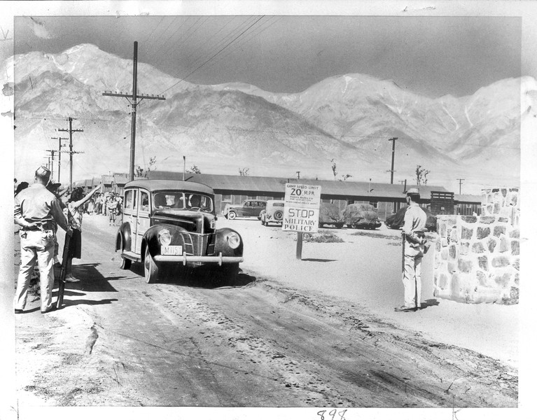 """""""On Way -- Here the Japs headed for the Nevada line and complete freedon, the crowded WRA station wagon passing through a military police sentry line.  The trip to Reno is made three times weekly.""""--caption on photograph"""