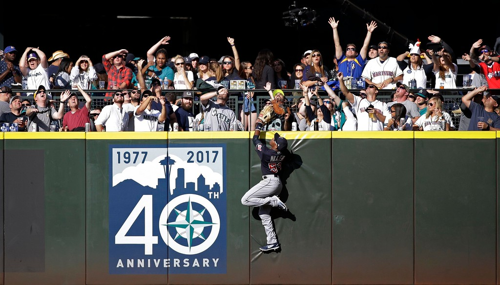 . Cleveland Indians center fielder Greg Allen climbs the wall as fans cheer and look up for a home run ball hit by Seattle Mariners\' Robinson Cano in the eighth inning of a baseball game Saturday, Sept. 23, 2017, in Seattle. (AP Photo/Elaine Thompson)