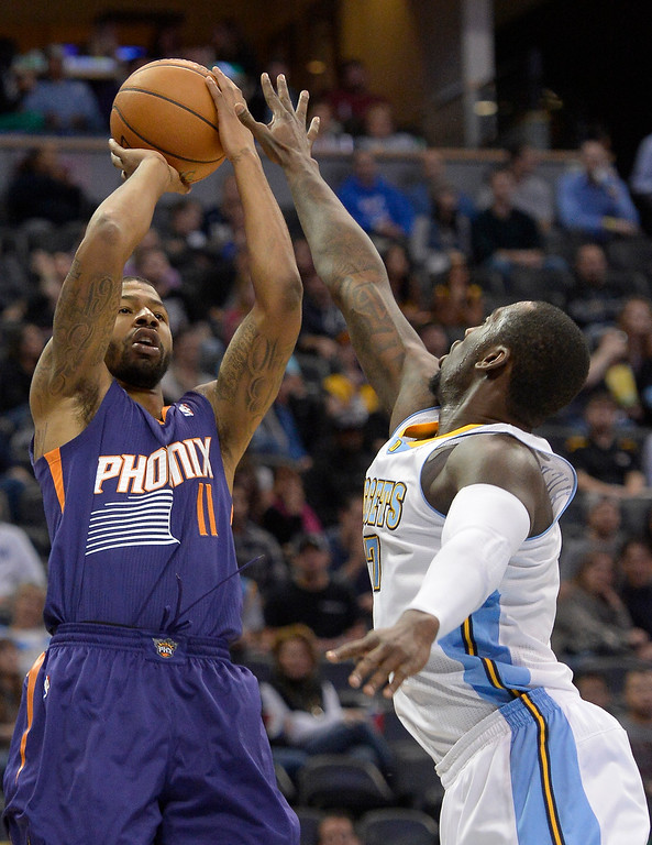 . Phoenix Suns power forward Markieff Morris (11) takes a shot over Denver Nuggets power forward J.J. Hickson (7) during the third quarter October 23, 2013 at Pepsi Center. (Photo By John Leyba/The Denver Post)