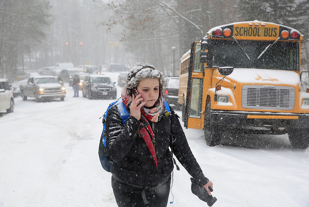 . Katharine Newton, a student at the University of North Carolina at Chapel Hill, calls her parents while walking more than two miles from campus to her parents\' home during a snow storm in Chapel Hill, NC, on Wednesday, Feb. 12, 2014.  Roads were blocked and Newton was unable to drive.  (AP Photo/Ted Richardson)