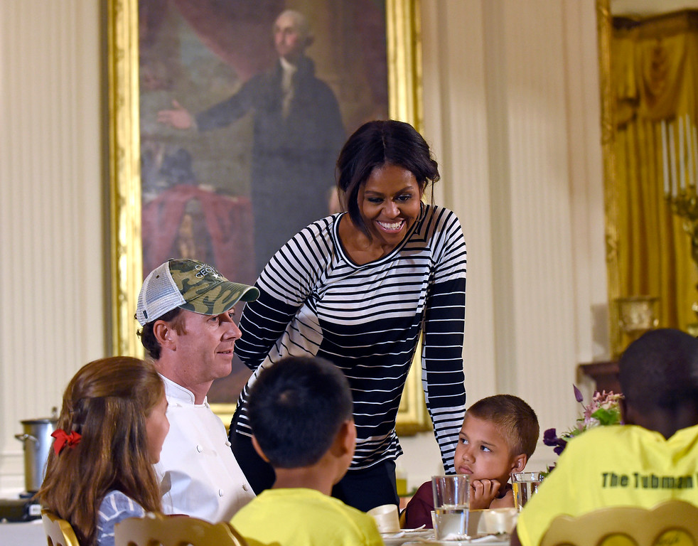 . First lady Michelle Obama talks with school children as they eat lunch in the East Room of the White House following the annual fall harvest of the White House Kitchen Garden in Washington, Tuesday, Oct. 14, 2014. Chef Geoff Tracy second from left, sits at the table. In celebration of Farm to School Month, the Obama invited students from Arizona, California, and Ohio to participate in the fall harvest. These schools were selected because they are participating in farm to school programs that incorporate fresh, local food into their school meals, and they teach students about healthy eating through school gardens and nutrition education.(AP Photo/Susan Walsh)