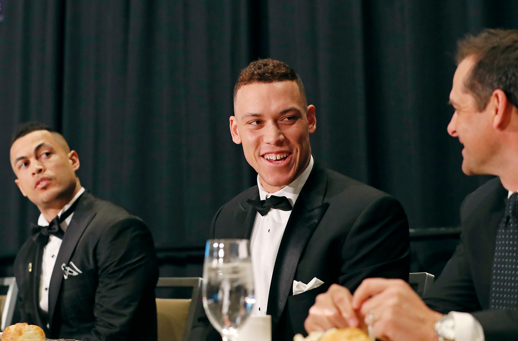 . National League Most Valuable Player Giancarlo Stanton, left, watches as American League Rookie of the Year Aaron Judge, center, talks to newly named New York Yankees manager Aaron Boone during the New York Chapter of the Baseball Writers\' Association of America annual dinner in New York, Sunday, Jan. 28, 2018, where both Stanton and Judge picked up their awards. Stanton, who signed with the New York Yankees in the off-season. joins Judge to form a powerful Yankees lineup. (AP Photo/Kathy Willens)