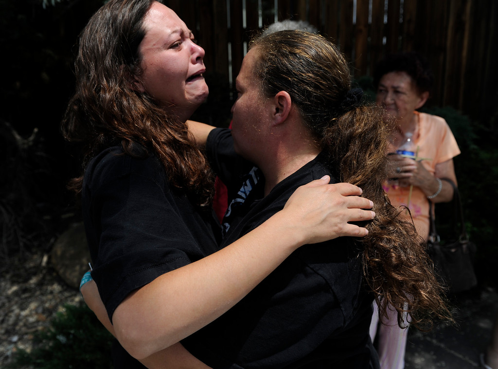 . Monique Gallegos, left, gets consoled by a friend near 92nd Ave and Westminster Blvd Thursday afternoon June 13, 2013 near the scene of the house explosion. Gallegos was in her home on the 9200 block of Ingalls Street with her mother when a house a few houses down from her exploded sending debris all over the neighborhood. (Photo By Andy Cross/The Denver Post)